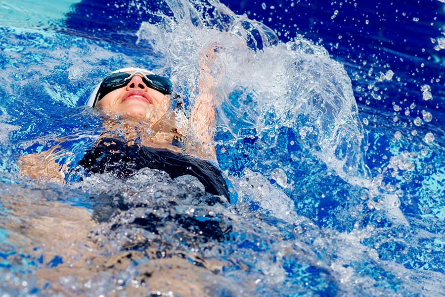 Young woman swimming back stroke