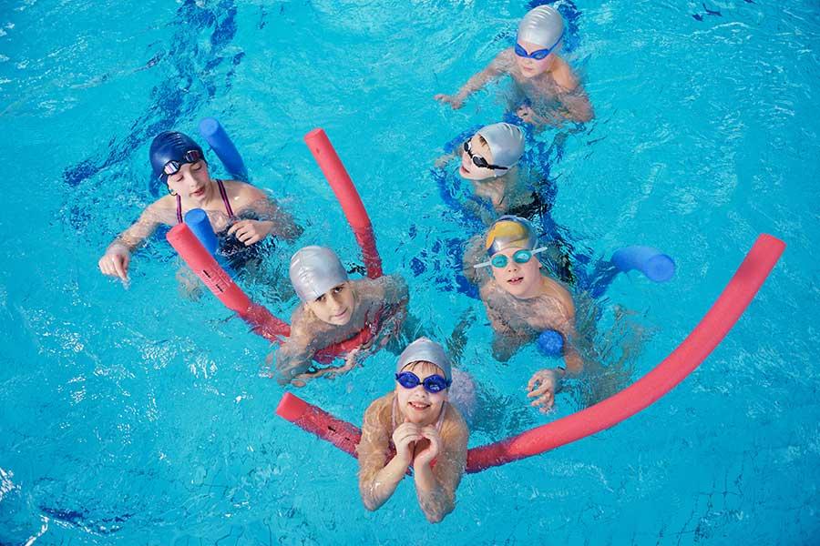 Children swimming class in swimming pool