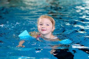 Young girl swimming with blue armbands